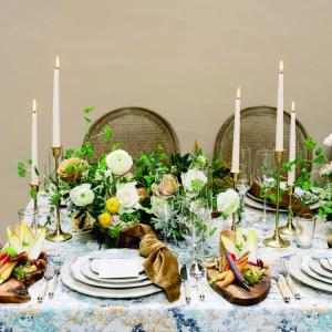 Table setting with candles, florals and shades of blues and green.