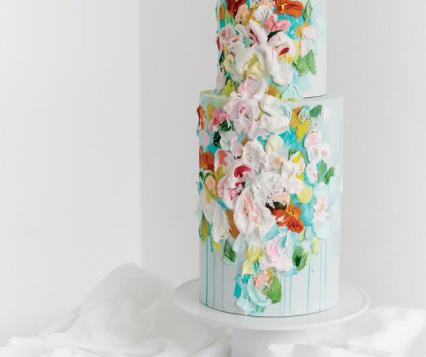 Modern wedding cake with artistic splashes of color in bright, floral hues.