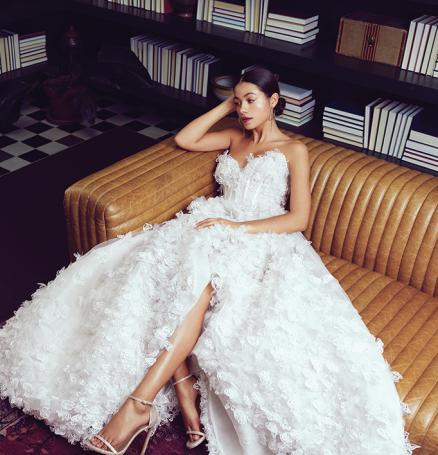 "Bride lounging in library in butterfly applique Luly Yang ""Butterfly Me to the Moon"" gown."