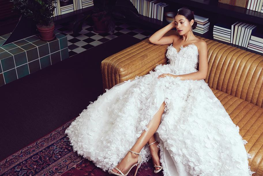 """Bride lounging in library in butterfly applique Luly Yang """"Butterfly Me to the Moon"""" gown."""
